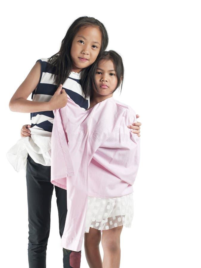 Menina asiática da criança de duas irmãs isolada no fundo branco imagem de stock