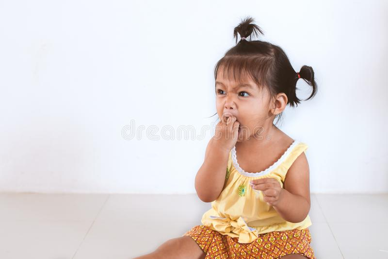 Menina asiática da criança do bebê que come o macarronete só e que faz uma confusão em suas cara e mão foto de stock royalty free