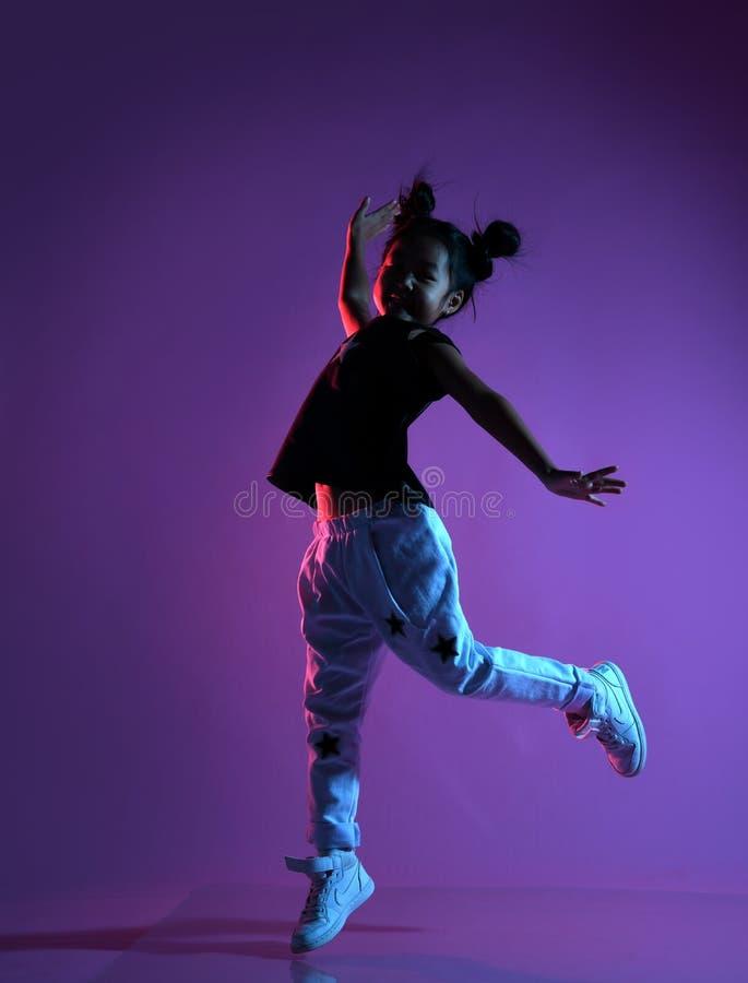 Menina asiática da criança na camisa e nas calças com danças das estrelas como uma estrela do disco fotos de stock royalty free