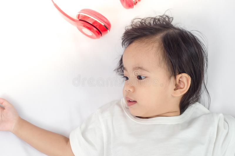 Menina asiática da criança que encontra-se na cama em casa fotografia de stock