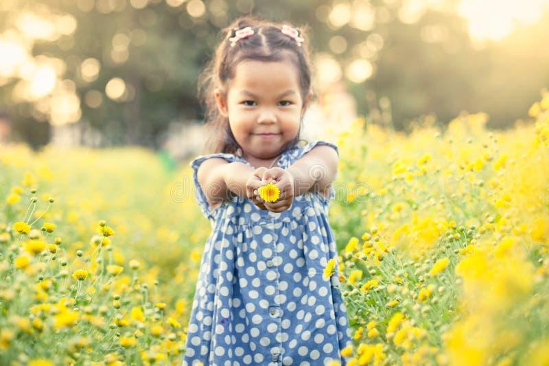 Menina asiática da criança que guarda a flor em sua mão no jardim fotografia de stock royalty free