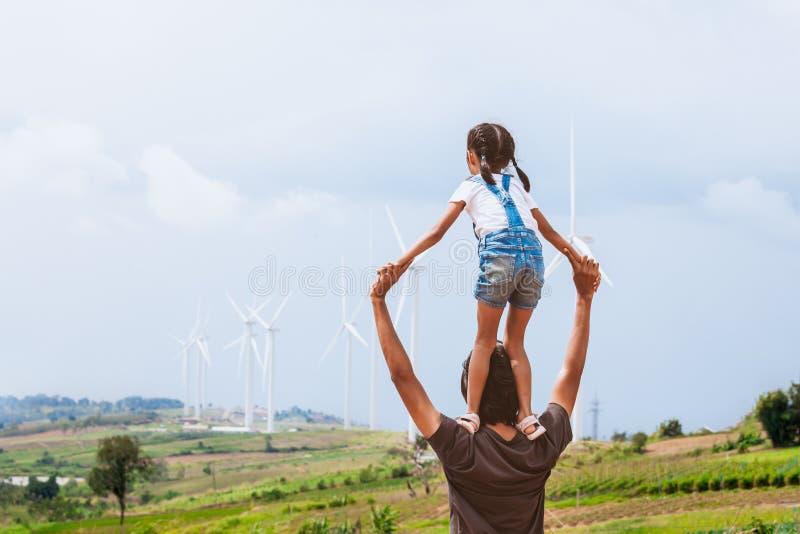 Menina asiática da criança que monta nos ombros do pai no campo da turbina eólica fotografia de stock royalty free