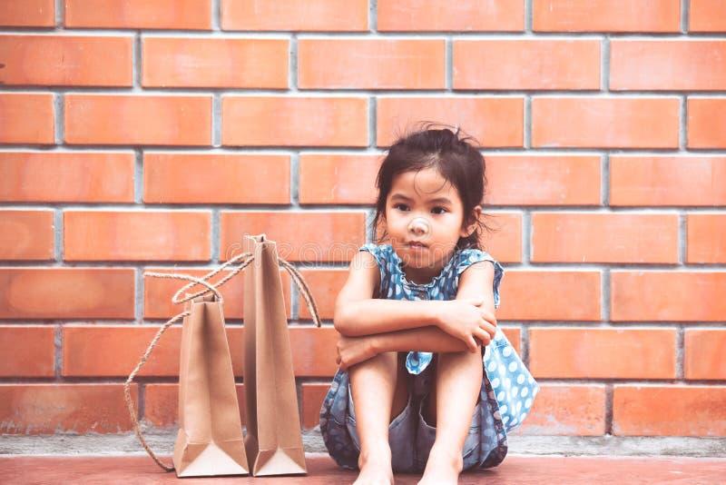 A menina asiática da criança que sente furou o assento e o aperto de seus joelhos fotos de stock