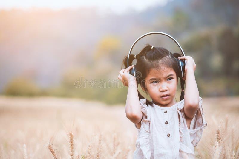 Menina asiática da criança que tem o divertimento a escutar a música com os fones de ouvido no campo da cevada com felicidade fotografia de stock