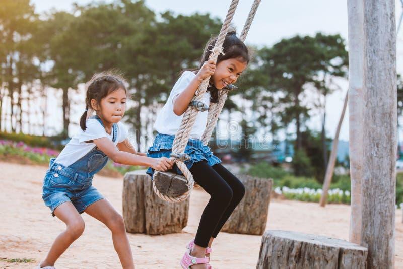Menina asiática da criança que tem o divertimento a jogar em balanços de madeira com sua irmã no campo de jogos com natureza boni imagens de stock royalty free