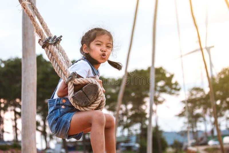 Menina asiática da criança que tem o divertimento a jogar em balanços de madeira no campo de jogos com natureza bonita imagem de stock