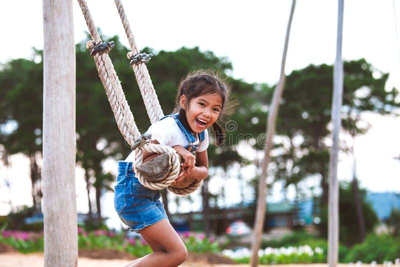 Menina asiática da criança que tem o divertimento a jogar em balanços de madeira no campo de jogos com natureza bonita fotografia de stock royalty free