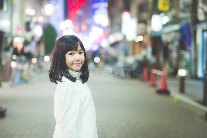 Menina asiática da menina que anda na rua da cidade da noite fotos de stock royalty free