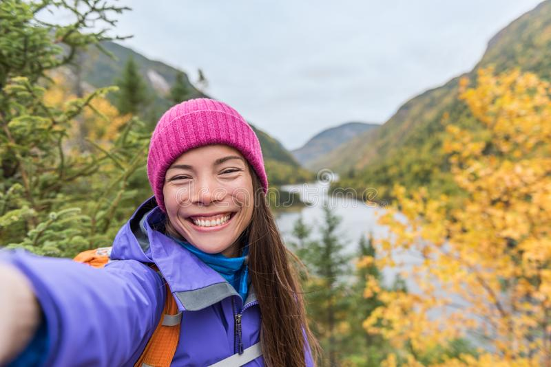 Menina asiática de Selfie que caminha em montanhas da natureza do outono Mulher feliz do caminhante que toma o telefone da terra  imagem de stock royalty free