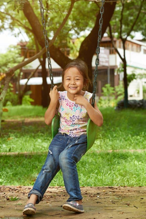 Menina asiática de sorriso em balanços foto de stock