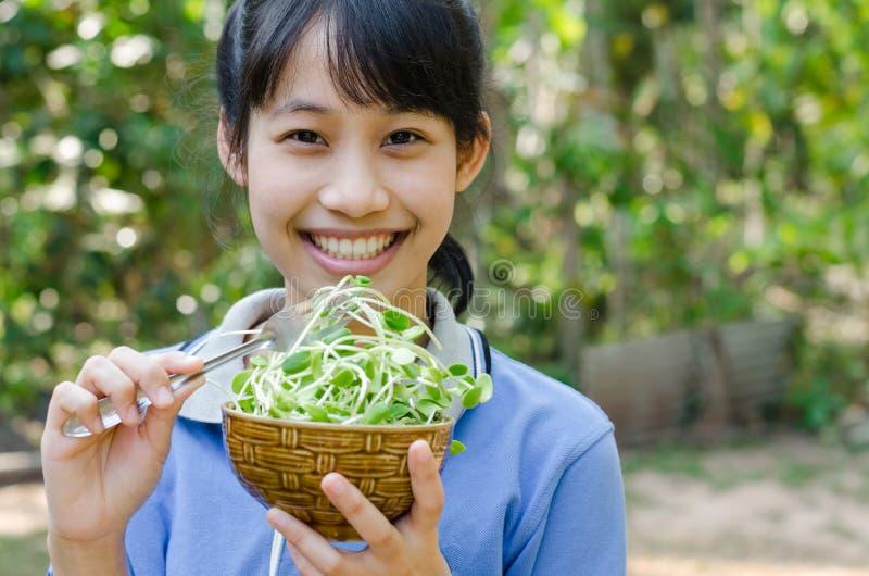 Menina asiática do adolescente feliz com os brotos vegetais do girassol foto de stock