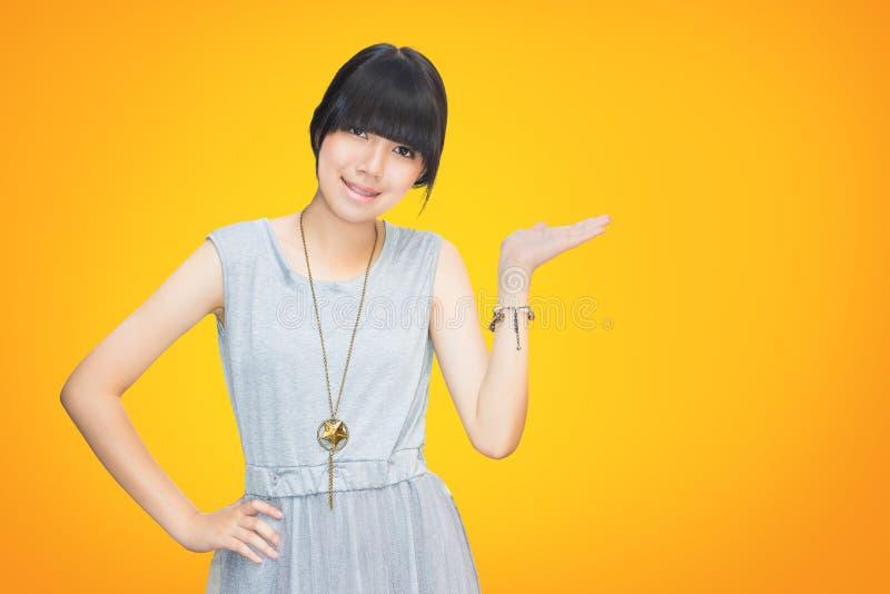 Menina asiática do adolescente que mostra a mão vazia foto de stock