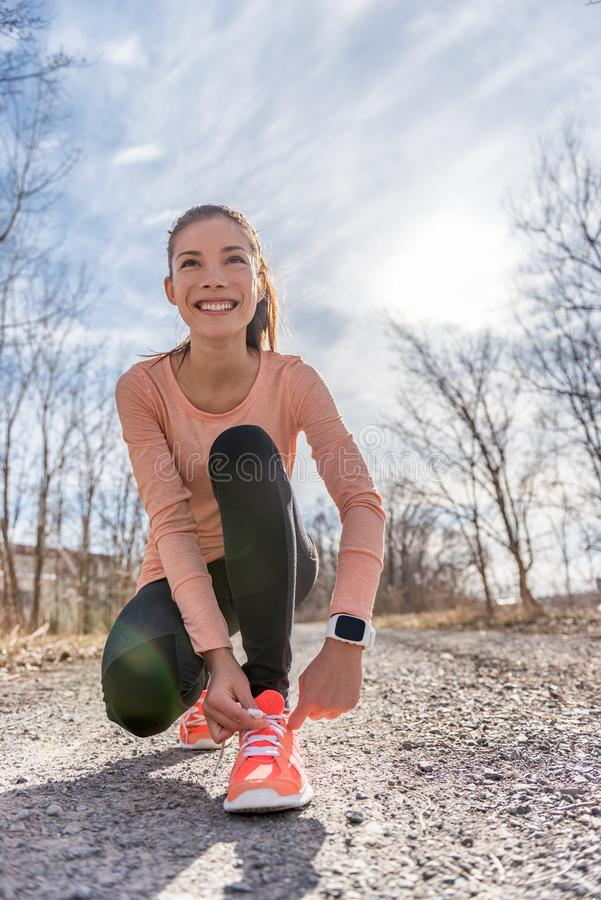 Menina asiática do corredor da fuga do outono que amarra os tênis de corrida que vestem a engrenagem do dispositivo do smartwatch fotografia de stock royalty free
