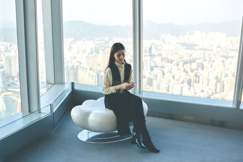 A menina asiática do moderno está usando o telefone de pilha, quando se sentar no interior luxuoso contra a janela com opinião da imagens de stock royalty free