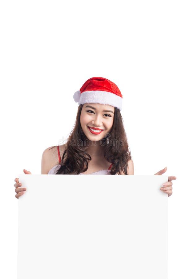 A menina asiática do Natal com Santa Claus veste guardar o sinal vazio foto de stock
