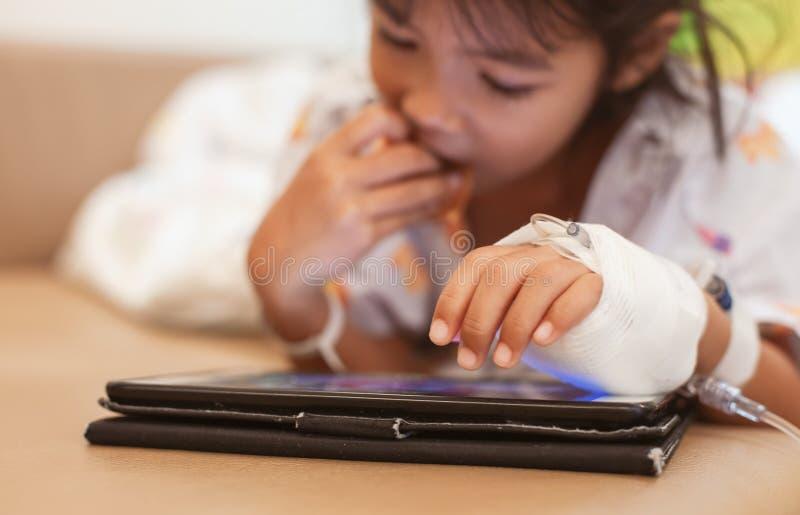 Menina asiática doente da criança pequena que tem a solução IV enfaixada jogando a tabuleta digital para relaxar fotos de stock royalty free