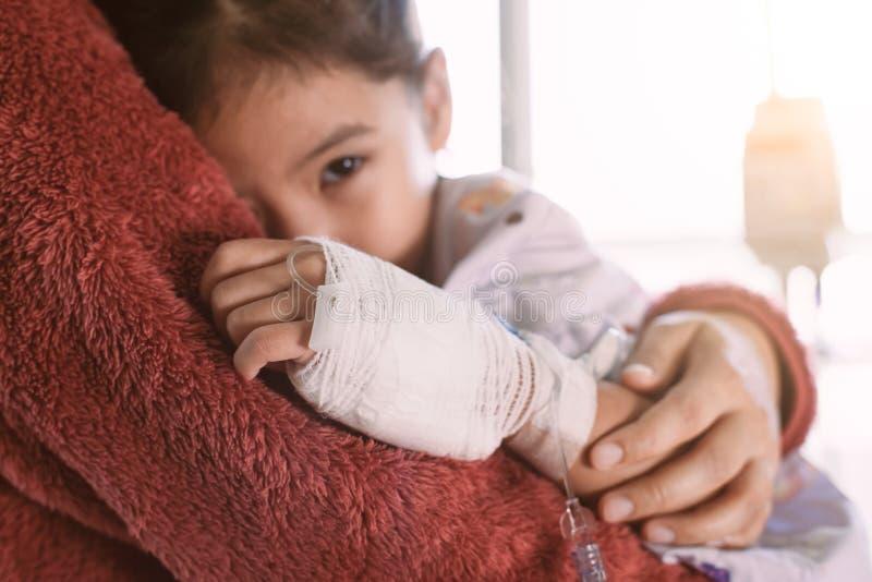 Menina asiática doente da criança que tem a solução IV que abraça sua mãe fotos de stock