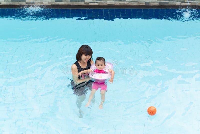 Menina asiática e mãe bonitos da criança que jogam na associação fotografia de stock