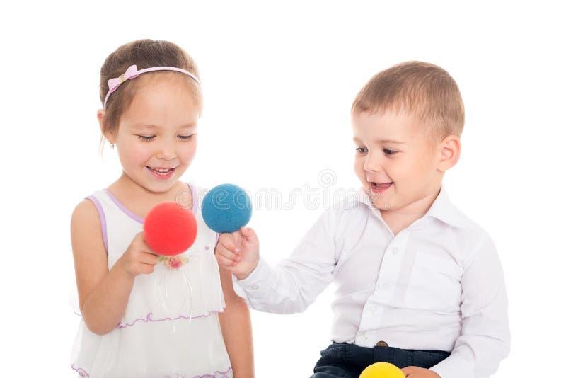 Menina asiática e menino europeu que jogam com bolas fotografia de stock