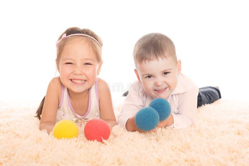 Menina asiática e menino europeu que jogam com bolas fotografia de stock royalty free