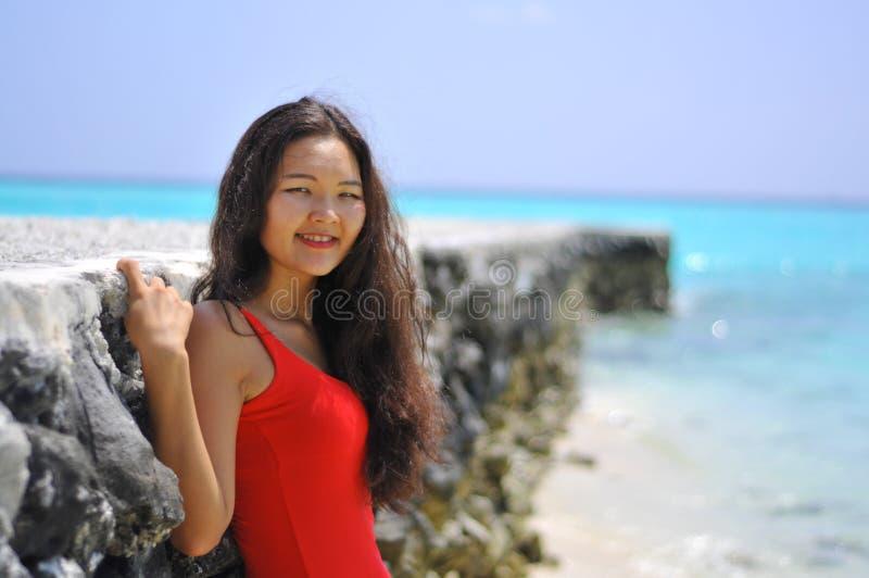 Menina asiática em um vestido vermelho perto do cais na praia tropical foto de stock