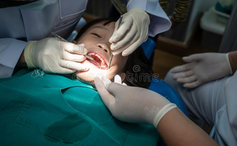A menina asiática encontrou o dentista para o controle dental rotineiro e o consultante imagem de stock royalty free