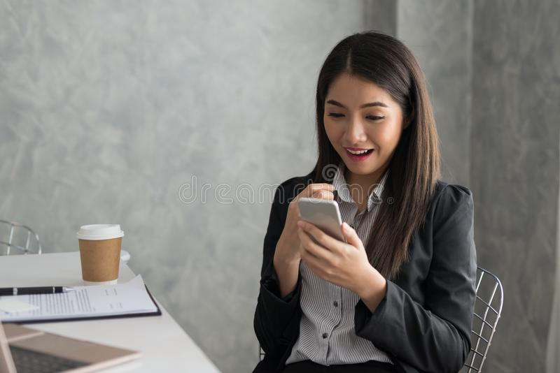 Menina asiática entusiasmado do negócio ao ler um assento esperto do telefone fotografia de stock