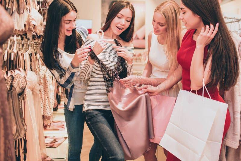A menina asiática está guardando a camisa da noite do laço É muito bonito As meninas estão olhando esta camisa também e estão toc fotos de stock royalty free