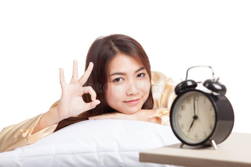 A menina asiática feliz acorda a APROVAÇÃO da mostra com despertador imagens de stock
