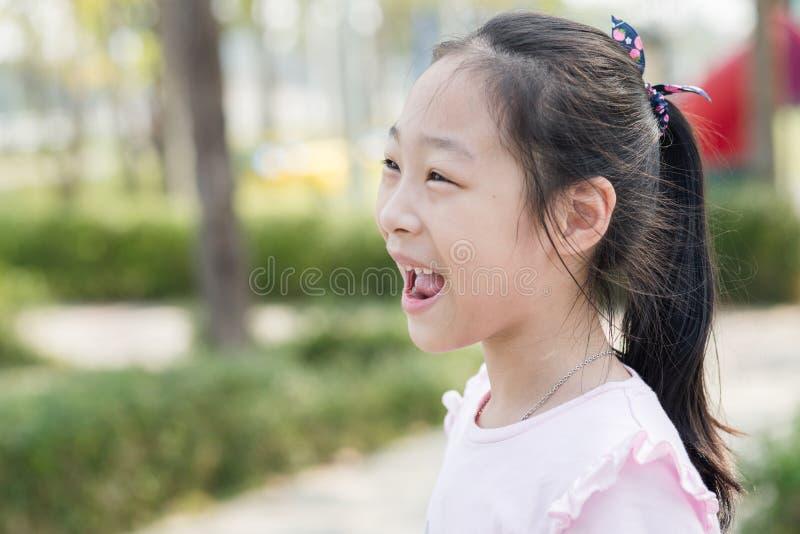 Menina asiática feliz no campo de jogos exterior imagem de stock royalty free
