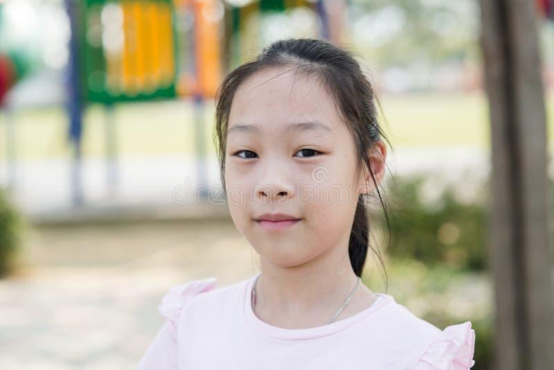 Menina asiática feliz no campo de jogos exterior imagens de stock