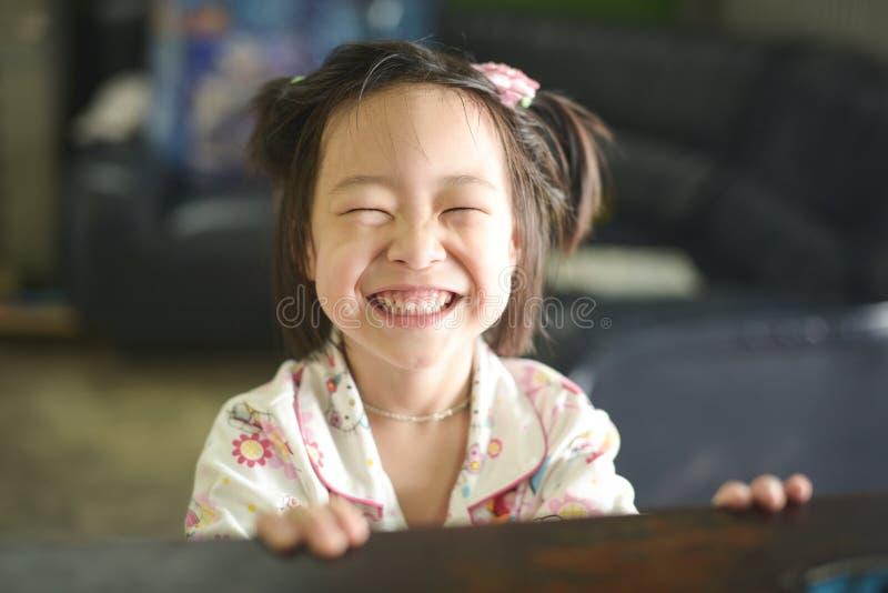 Menina asiática feliz no sorriso dos pijamas fotografia de stock
