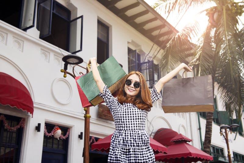 Menina asiática feliz nos óculos de sol que guardam sacos de compras imagem de stock royalty free