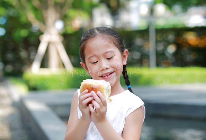 Menina asiática feliz que come o pão com a sobremesa Morango-enchida enchida no jardim exterior fotos de stock