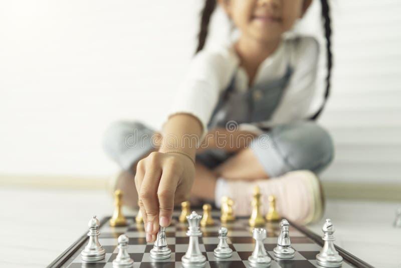 Menina asiática feliz que joga a xadrez em casa fotos de stock