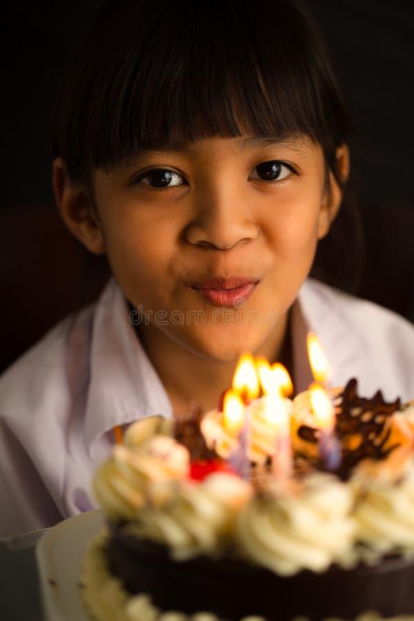 A menina asiática funde para fora as velas foto de stock royalty free
