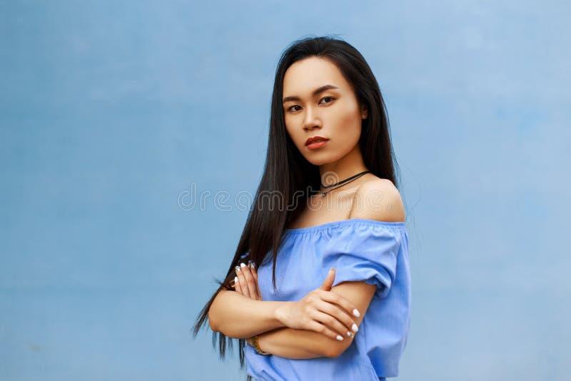 A menina asiática moreno bonita com cabelo longo dobrou sua mão fotografia de stock royalty free
