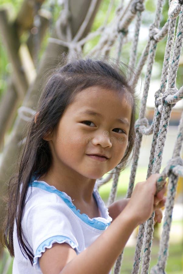 Menina asiática na escada de escalada no campo de jogos imagem de stock royalty free