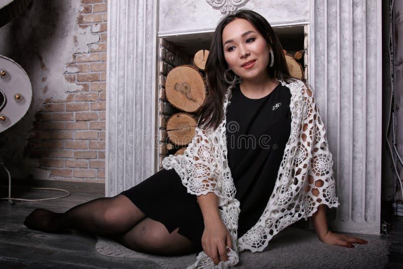 Menina asiática na meia-calça rasgada que senta-se perto da chaminé com o xaile em seus ombros foto de stock royalty free