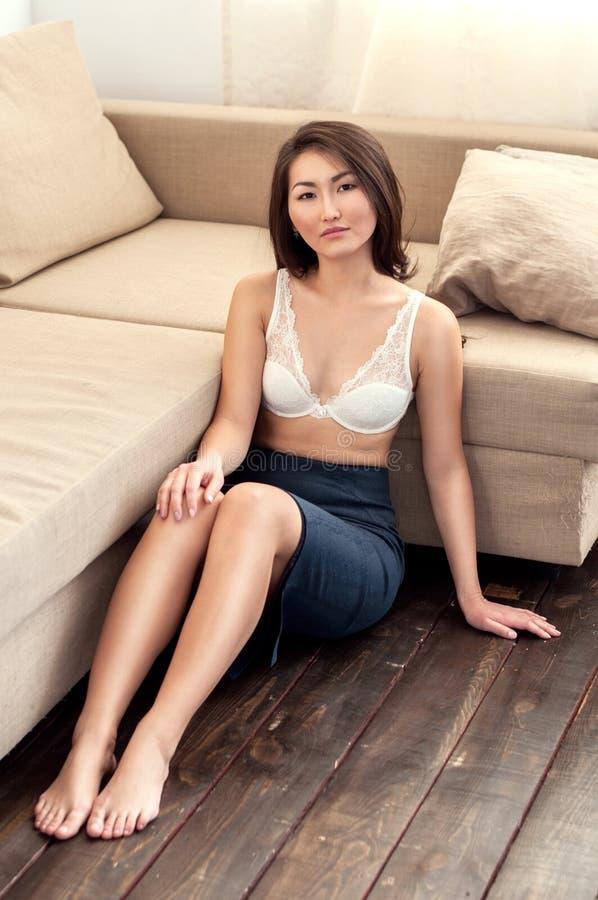 Menina asiática na saia que senta-se no assoalho imagens de stock royalty free