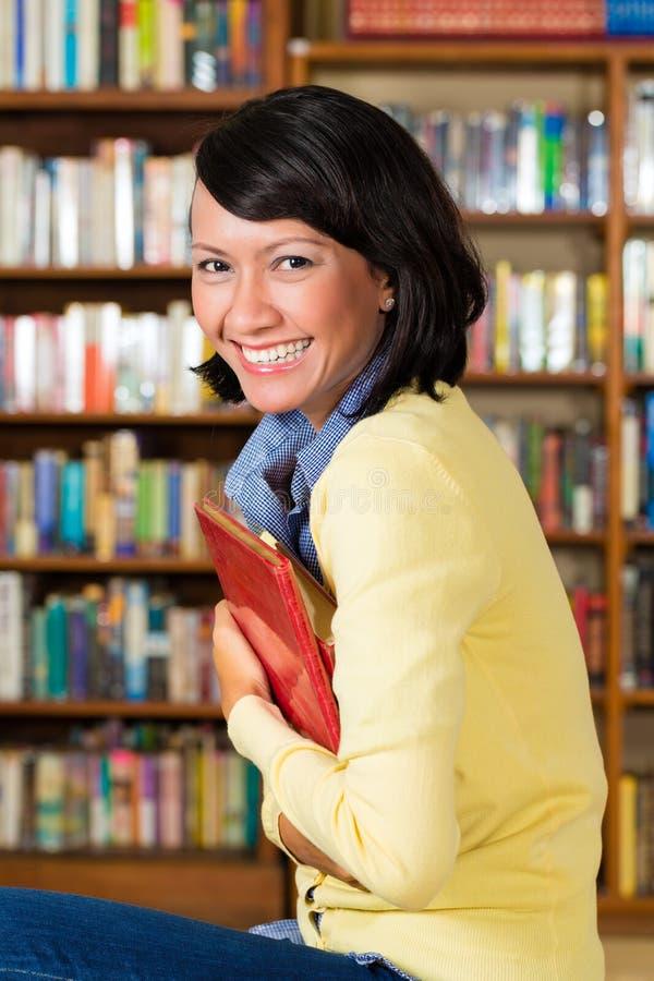 Menina asiática na terra arrendada de biblioteca um livro imagem de stock royalty free