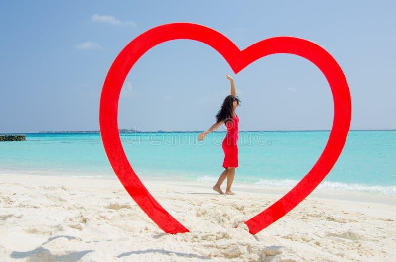 Menina asiática nas mãos de aumentação de um vestido vermelho na praia tropical dentro do coração fotografia de stock
