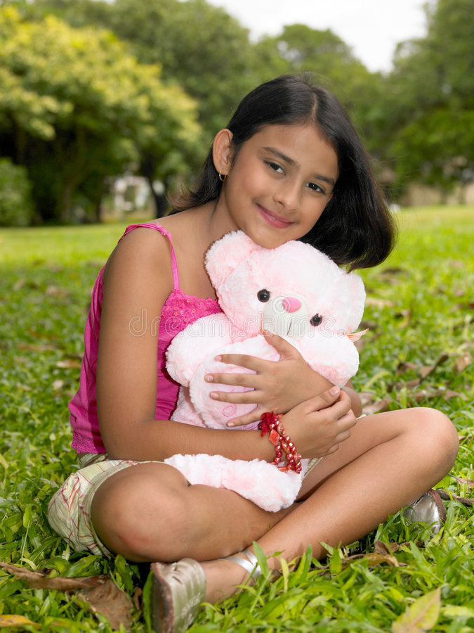 Menina asiática no jardim com seu urso de peluche cor-de-rosa fotos de stock