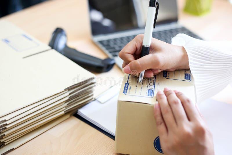 A menina asiática nova é começo do freelancer acima do endereço pequeno da escrita do proprietário empresarial na caixa de cartão imagens de stock