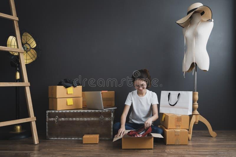 A menina asiática nova é freelancer com seu escritório do assunto privado em casa, trabalhando com portátil, café, mercado em lin imagens de stock