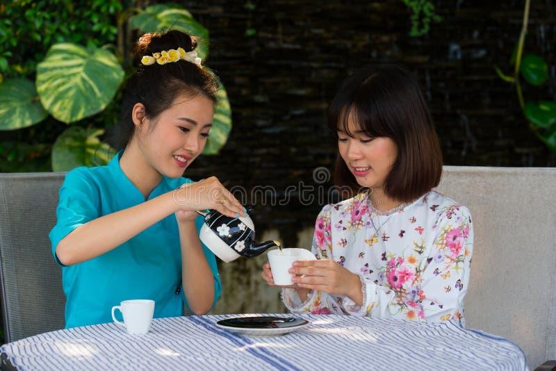 A menina asiática nova bonita aprecia o jardim exterior do partido do café imagem de stock