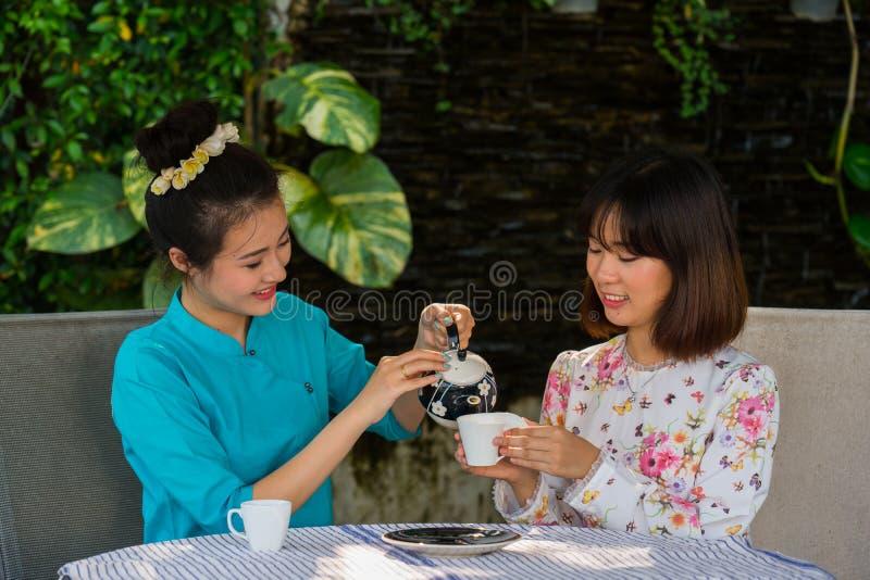 A menina asiática nova bonita aprecia o jardim exterior do partido do café fotografia de stock
