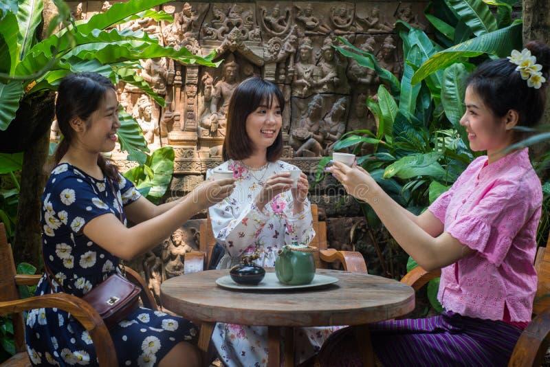 A menina asiática nova bonita aprecia o templo exterior do partido do café foto de stock royalty free