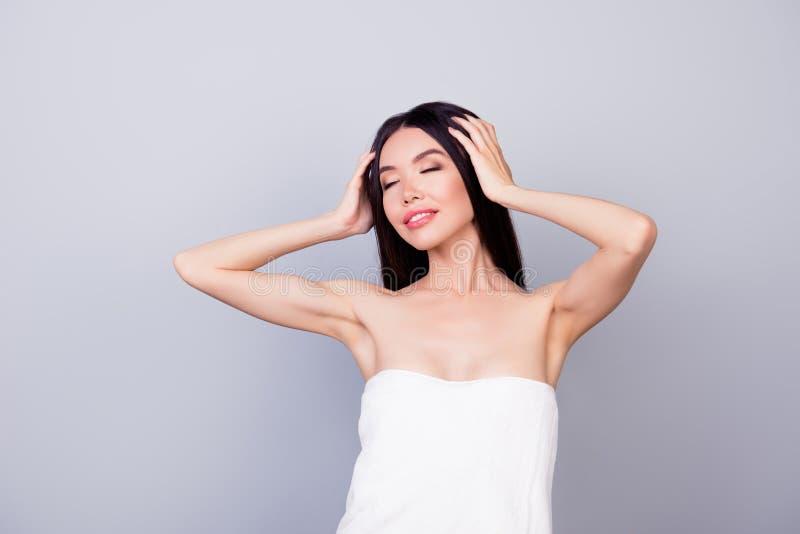 A menina asiática nova bonita, envolvida em uma toalha branca é tocante seu cabelo na luz - fundo cinzento, tão encantador e feli imagens de stock