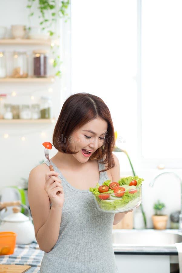 Menina asiática nova bonita que come a salada imagem de stock royalty free